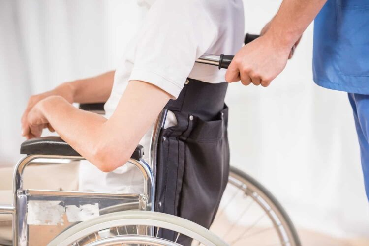 man pushed in wheelchair